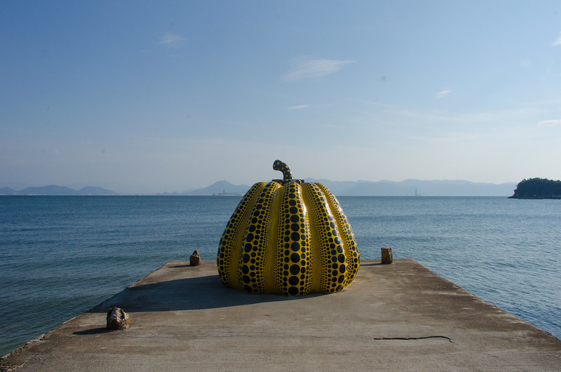Giant yellow and black polka dot printed pumpkin by the sea shore.