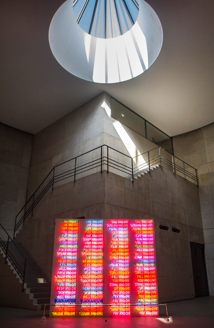 Bright pink light artwork in gallery with sun shining down through the roof.